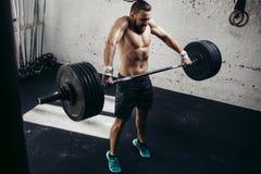 Pesi di sollevamento dell'uomo Allenamento muscolare dell'uomo in palestra che fa gli esercizi con il bilanciere Immagini Stock