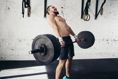 Pesi di sollevamento dell'uomo Allenamento muscolare dell'uomo in palestra che fa gli esercizi con il bilanciere Immagine Stock Libera da Diritti