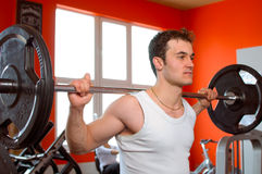 Pesi di sollevamento dell'uomo a ginnastica Fotografie Stock