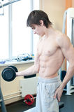 Pesi di sollevamento dell'uomo muscolare potente in ginnastica Fotografie Stock