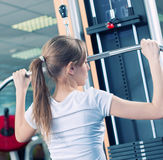 Pesi di sollevamento della donna casuale potente in ginnastica Immagine Stock