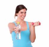 Pesi di sollevamento e bottiglia di acqua della giovane donna adatta Fotografia Stock