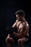 Pesi di sollevamento muscolari del giovane su fondo nero Immagini Stock