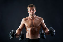 Pesi di sollevamento muscolari del giovane su fondo nero Fotografia Stock