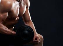 Pesi di sollevamento muscolari del giovane su fondo nero Fotografie Stock Libere da Diritti