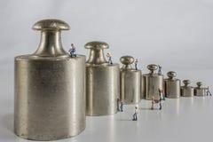 Pesi per equilibrio con i lavoratori miniatura Fotografie Stock