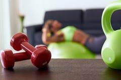 Pesi rossi di forma fisica domestica sugli ABS di addestramento della donna e della Tabella fotografia stock
