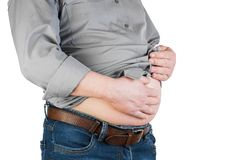 Peso corporal adicional de um homem com suas mãos que tocam na gordura em seu s imagem de stock