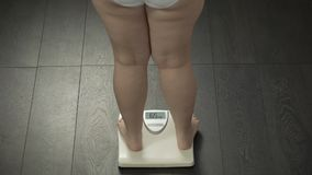 Peso corporal ideal, mulher que pisa em escalas para medir fazer dieta o resultado, traseiro filme