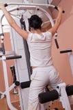 Peso de elevación de la muchacha en el aparato de la gimnasia Fotografía de archivo
