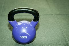 Peso de Kettlebell no assoalho preto do gym com grão do foco seletivo e do filme Fotos de Stock