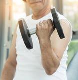 Peso de levantamento asiático do homem superior no gym Foto de Stock
