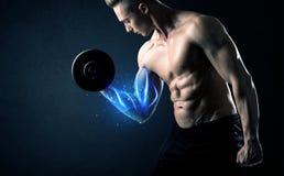 Peso de levantamento do atleta apto com conceito azul da luz do músculo fotografia de stock