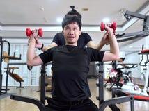 Peso de levantamento do homem asiático novo saudável com o instrutor pessoal no gym do esporte Conceito da aptidão e do exercício fotos de stock royalty free