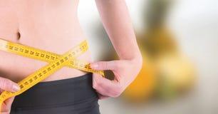 Peso de medición de la mujer con la cinta métrica en la cintura en la playa del verano foto de archivo