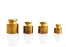 Peso di colore dell'oro su un fondo bianco Fotografia Stock