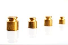 Peso di colore dell'oro su un fondo bianco Fotografie Stock
