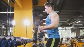 Peso-levantamento no gym - o atleta muscular executa o treinamento para o bíceps com os pesos Fotografia de Stock Royalty Free