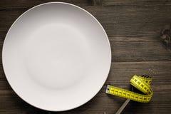 Peso perdidoso Dieta estricta Placa y cinta métrica vacías en de la bifurcación la comida en lugar de otro en maqueta de madera d Fotos de archivo libres de regalías