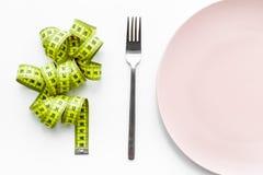 Peso perdidoso Dieta estricta Placa y cinta métrica vacías en la maqueta blanca de la opinión superior del fondo Imagen de archivo