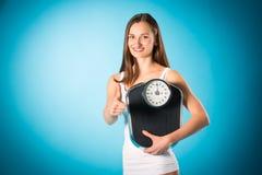 Peso perdidoso - mujer joven con la escala de medición Imágenes de archivo libres de regalías