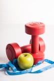 Peso rosso delle teste di legno con nastro adesivo di misurazione e la mela verde fotografia stock