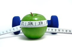 Pesos azules, Apple verde, y cinta métrica Imagen de archivo libre de regalías