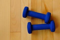 Pesos azules en el suelo de madera dura del centro de aptitud Imagen de archivo