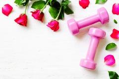 Pesos cor-de-rosa do esporte, e rosas vermelhas no fundo de madeira branco, Fotografia de Stock Royalty Free