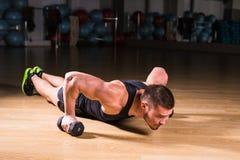 Pesos de Doing Pushups With do atleta do homem novo como parte do treinamento do halterofilismo Imagens de Stock