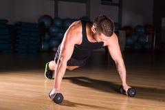 Pesos de Doing Pushups With do atleta do homem novo como parte do treinamento do halterofilismo Imagem de Stock