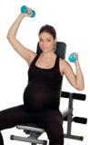 Pesos de elevación de la mujer embarazada en el gimnasio Fotos de archivo libres de regalías