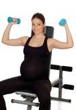 Pesos de elevación de la mujer embarazada en el gimnasio Imágenes de archivo libres de regalías
