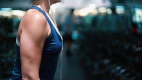Pesos de elevación de la mujer en el gimnasio, resolviéndose los brazos almacen de video