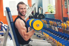 Pesos de elevación del atleta joven en el gimnasio Imagen de archivo libre de regalías