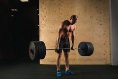Pesos de elevación del hombre Entrenamiento muscular del hombre en el gimnasio que hace ejercicios con el barbell Fotografía de archivo