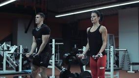 Pesos de elevación del hombre joven y de la mujer en un gimnasio metrajes