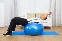 Pesos de elevación del hombre que ejercitan en la bola de Pilates Fotos de archivo libres de regalías