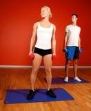 Pesos de elevación del hombre y de la mujer en gimnasia Fotografía de archivo