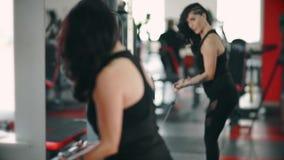 Pesos de elevación de la mujer morena fuerte en un gimnasio almacen de video