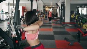 Pesos de elevación de la mujer morena fuerte en un gimnasio almacen de metraje de vídeo