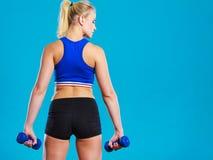 Pesos de elevación de las pesas de gimnasia de la mujer apta Imágenes de archivo libres de regalías