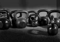 Pesos de Kettlebells em um gym do exercício