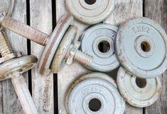 Pesos de la pesa de gimnasia del equipo de la aptitud en viejo fondo de madera imagen de archivo