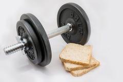 Pesos de la pesa de gimnasia del equipo del ejercicio de la aptitud y tres rebanadas del pan fresco Foto de archivo libre de regalías