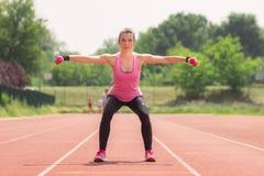 Pesos de la posición en cuclillas del atleta de la muchacha Fotos de archivo