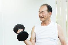 Pesos de levantamento asiáticos do homem superior no gym Fotografia de Stock