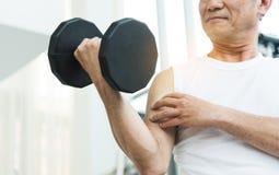 Pesos de levantamento asiáticos do homem superior no gym Foto de Stock Royalty Free