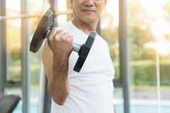 Pesos de levantamento asiáticos do homem superior no gym Imagens de Stock Royalty Free