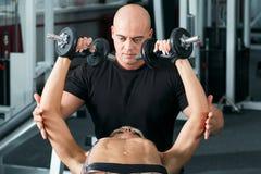 Pesos de levantamento da mulher com seu instrutor pessoal no gym Fotos de Stock